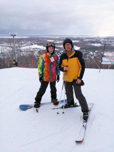 Snowboarder and Alpine Skier in Blue Mountaint